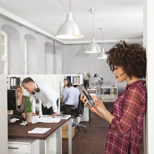 Woman in office using digital tablet with colleagues in background